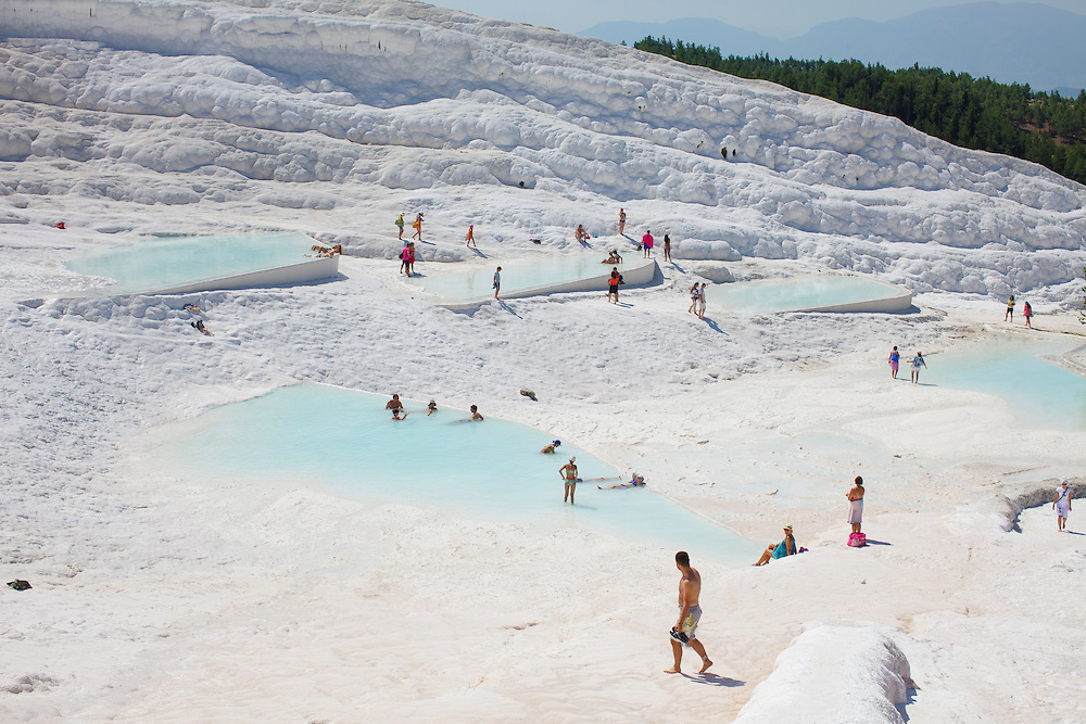 A view of the white terraced hill  at Pamukkale. The hard, white mineral deposits, which from a distance resemble snow, are caused by the high mineral content of the natural spring water which runs down the cliff and congregates in warm pools on the terraces. This is such a popular tourist attraction that strict rules had to be established in order to preserve its beauty, which include the fact that visitors may no longer walk on the terraces. Those who want to enjoy the thermal waters, however, can take a dip in the nearby pool, littered with fragments of marble pillars.