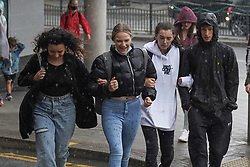 © Licensed to London News Pictures. 28/07/2021. Sheffield, UK. Students brave the rain in Sheffield as parts of Yorkshire are hit by heavy rain and thunderstorms. Photo credit: Ioannis Alexopoulos/LNP