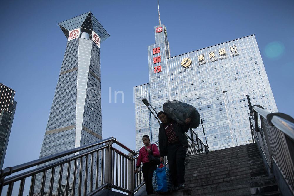 Pedestrians walk over a bridge in Shenzhen, China, on Thursday, Dec. 17, 2015.