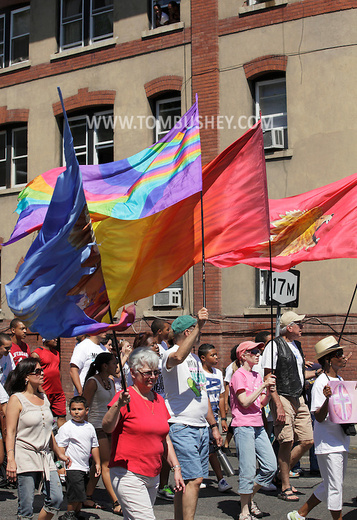 Middletown, New York - People, including some carrying flags, walk down the street during a March for Jesus on July 9, 2011.