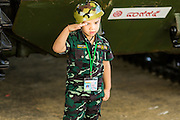 """11 JANUARY 2014 - BANGKOK, THAILAND: A boy dressed as a soldier salutes during Children's Day in Bangkok. The Royal Thai Army hosted a """"Children's Day"""" event at the 2nd Cavalry King's Guard Division base in Bangkok. Children had an opportunity to look at military weapons, climb around on tanks, artillery pieces and helicopters and look at battlefield medical facilities. The Children's Day fair comes amidst political strife and concerns of a possible coup in Thailand. Earlier in the week, the Thai army announced that movements of armored vehicles through Bangkok were not in preparation of a coup, but were moving equipment into position for Children's Day.      PHOTO BY JACK KURTZ"""