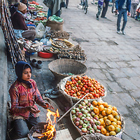 A boy warms his feet as he tries to sell vegetables in the Kathmandu Bazaar, 1986.