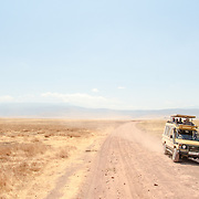 A safari vehicle sits on the side of the dirt track at Ngorongoro Crater in the Ngorongoro Conservation Area, part of Tanzania's northern circuit of national parks and nature preserves.