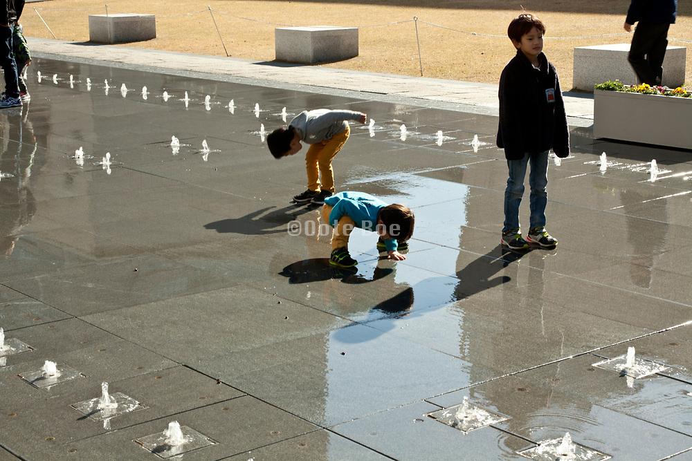 little children playing in a water fountain Yokohama Japan