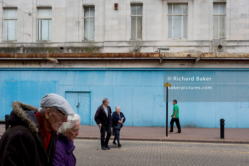 A passer-by using his phone walks past the blue hoarding outside a closed entertainment venue in Dartford, on 3rd October 2019, in Dartford, Kent, England. Voters in Dartford voted 64% in favour of Brexit during the 2016 referendum.