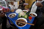 Lunch in one of many small sidewalk restaurants in Hanoi, Vietnam.