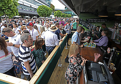 People queuing for drinks on day one of the Wimbledon Championships at the All England Lawn Tennis and Croquet Club, London.