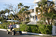 Tourists riding around Dunmore Town in a gold cart.  Harbour Island, Eleuthera,<br /> The Bahamas