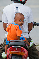 A young boy rides on the back of his father's motocycle in Dili, Timor-Leste (East Timor)