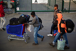 © Licensed to London News Pictures. 25/10/2016. Calais, France.  Migrants carry and push their belongings as they leave the 'Jungle' camp to board a bus. French authorities have moved thousands of refugees and migrants living at the makeshift living area on the French coast, with some still refusing to leave. . Photo credit: Ben Cawthra/LNP