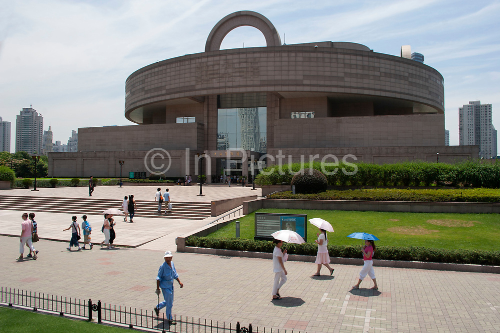 Shanghai Museum in Peoples Square, downtown Shanghai, China. People shielding themselves from the sun with umbrellas walk past this popular museum on a sunny summer day.