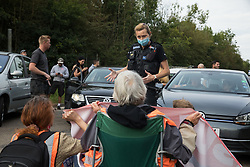 Godstone, UK. 13th September, 2021. A Surrey Police officer asks climate activists from Insulate Britain to move out of a slip road from the M25, causing long tailbacks on the motorway, as part of a new campaign intended to push the UK government to make significant legislative change to start lowering emissions. The activists, who wrote to Prime Minister Boris Johnson on 13th August, are demanding that the government immediately promises both to fully fund and ensure the insulation of all social housing in Britain by 2025 and to produce within four months a legally binding national plan to fully fund and ensure the full low-energy and low-carbon whole-house retrofit, with no externalised costs, of all homes in Britain by 2030 as part of a just transition to full decarbonisation of all parts of society and the economy.