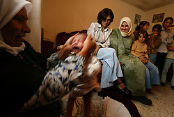 """Leith Lamour, who's first name means """"lamb,"""" is picked up by his head while being stretched after having his head and neck massaged with olive oil by his grandmother Helwa Lamour, Bethlehem, Palestinian Territories, Nov. 15, 2004. The olive oil, made from olives grown in local orchards, is supposed to help relax muscles. The baby was born two weeks prior."""