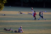 As the UK Coronavirus pandemic lockdown continues but with restrictions easing, south Londoners enjoy the last weekend sunshine by playing football and throwing a frisbee in Ruskin Park, a public green space in Lambeth, on 14th June 2020, in London, England.