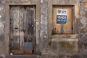 A derelict building lies vacant after many years but is now for sale by a local estate agent, on 17th July, at Aveira, Portugal. Across the country, and even at important tourist landmarks, both fine and modest buildings sit vacant and often collapsing. Sometimes it is because a previous generation have passed away to leave properties in the hands of arguing families. Beautiful buildings are therefore left to collapse in town centre.