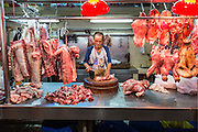 12 AUGUST 2013 - MACAU: A butcher cuts meat in a Macau wet market. Macau, also spelled Macao, is one of the two special administrative regions of the People's Republic of China (PRC), the other being Hong Kong. Macau lies on the western side of the Pearl River Delta across from Hong Kong to the east, bordered by Guangdong province to the north and facing the South China Sea to the east and south. The territory's economy is heavily dependent on gambling and tourism, but also includes manufacturing.     PHOTO BY JACK KURTZ