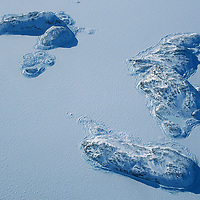 Small islands rise above the ice in a frozen fjord on Canada's Baffin Island, north of the Arctic Circle.