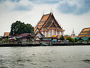 10 SEPTEMBER 2015 - BANGKOK, THAILAND:  Wat Kalayanamit as seen from the Chao Phraya River. Authorities started to destroy 54 homes in front of Wat Kalayanamit, a historic Buddhist temple on the Chao Phraya River in the Thonburi section of Bangkok. Government officials, protected by police, seized the house of Chaiyasit Kittiwanitchapant, a Kanlayanamit community leader, who has led protests against the temple's abbot for trying to evict community members whose houses are located around the temple. Work crews went into Chaiyasit's home and took it apart piece by piece. The abbot of the temple said he was evicting the residents, who have lived on the temple grounds for generations, because their homes are unsafe and because he wants to improve the temple grounds. The evictions are a part of a Bangkok trend, especially along the Chao Phraya River and BTS light rail lines, of low income people being evicted from their long time homes to make way for urban renewal.    PHOTO BY JACK KURTZ