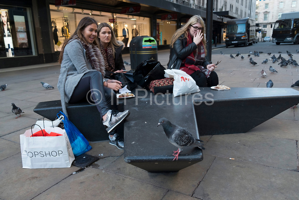 Pigeons gathering in large numbers in this small area just away from the bustle of Oxford Street in London, England, United Kingdom. Some girls trying to eat their lunch are harassed by the birds.
