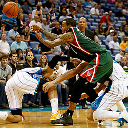 Dec 3, 2012; New Orleans, LA, USA; Milwaukee Bucks point guard Monta Ellis (11) loses the ball as he collides with New Orleans Hornets shooting guard Austin Rivers (25) and center Robin Lopez (15) during the second half of a game at the New Orleans Arena. The Hornets defeated the Bucks 102-81.  Mandatory Credit: Derick E. Hingle-USA TODAY Sports