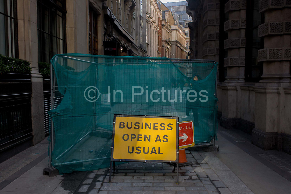 A sign saying that Business Open As Usual stands in a narrow City of London street. The fening partially blocks off this lane in the heart of the capital's financial district known as the Square Mile that was founded by the Romans in the 1st Century. Banking and insurance institutions populate this, the most ancient part of London whose streets have existed along the same paths and lines as many hundreds of years. Disruption is common as roadworks and improvements are forever changing the the city's landscape. Pedestrians have to walk around signage and construction fencing.