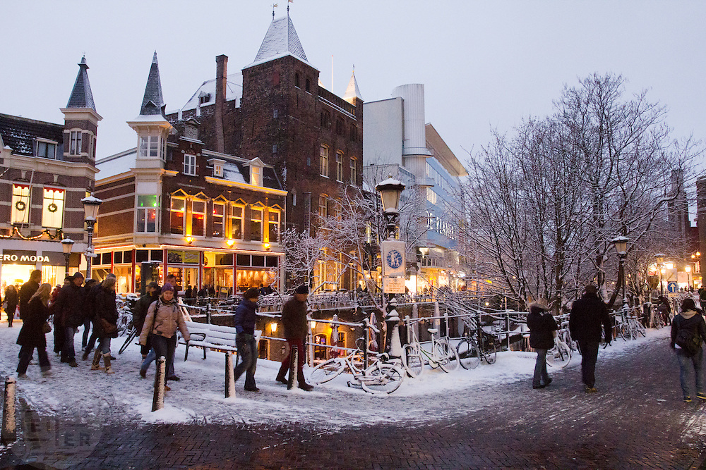 Voetgangers lopen in de schemer door een besneeuwd Utrecht.<br /> <br /> Pedestrians in a snowy Utrecht at twilight.