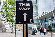 Pedestrians walk in the direction of a sign pointing straight ahead, a direction for something unknown happening this way, in a City of London sidestreet, on 22nd September 2021, in London, England.
