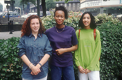 Multiracial group of teenage girls standing outdoors smiling,