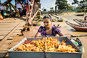 "17 JUNE 2013 - YANGON, MYANMAR: A vendor selling fried snacks on the Dala pier for the Yangon-Dala ferry. The ferry to Dala opposite Yangon on the Yangon River is the main form of transportation across the river. Every day the ferry moves tens of thousands of people across the river. Many working class Burmese live in Dala and work in Yangon. The ferry is also popular with tourists who want to experience the ""real"" Myanmar. The rides takes about 15 minutes. Burmese pay about the equivalent of .06¢ US for a ticket.  Foreigners pay about the equivalent of about $4.50 US for the same ticket.    PHOTO BY JACK KURTZ"
