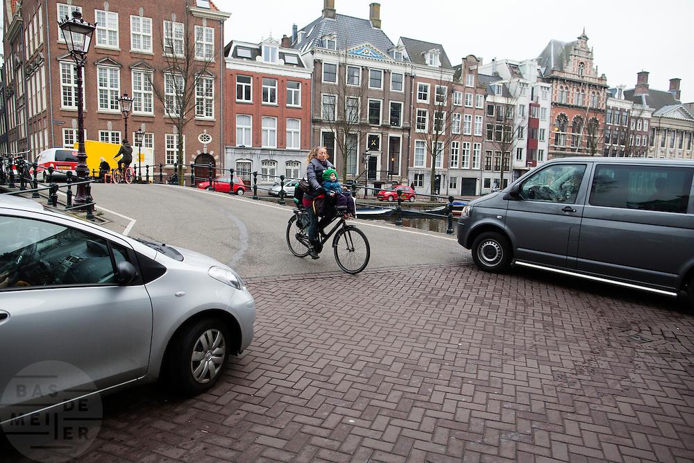 In Amsterdam rijdt een vrouw met een kindje voorop de fiets tussen twee auto's door.<br /> <br /> In Amsterdam a woman with a child on the front of the bike rides between two cars.