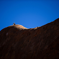 100414       Cable Hoover<br /> <br /> One spectator watches from the pinnacle of a sandstone butte during the Gallup High School cross-country race Saturday at Red Rock Park.