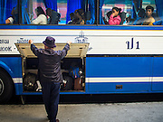 04 JANUARY 2015 - BANGKOK, THAILAND:  A bus driver closes the luggage compartment of a Pattaya bound bus at the Ekkamai Bus Station in central Bangkok. Buses from Ekkamai go to Chonburi, Rayong, and Trat provinces, including the resort city of Pattaya. Millions of Thais hit the road Sunday returning to Bangkok after the long weekend New Year holiday. Train stations and trains were packed and the state owned bus company scheduled thousands of extra buses to handle the demand.   PHOTO BY JACK KURTZ