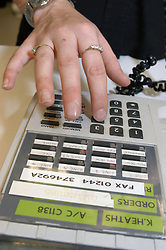 Shop worker using telephone in office; UK