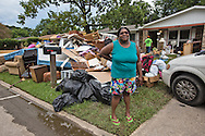 Iris Puris in front of her flooded home in Baton Rouge while it is being gutted.