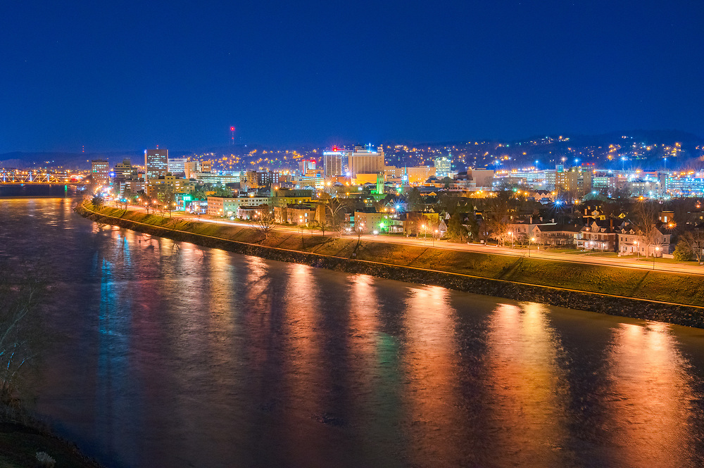 The lights of West Virginia's capital city of Charleston burn through the sky line as the reflected lights in the Kanawha River appear to melt into the water's surface.