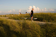 A jogger doing stretching exercises in South Pointe Park Miami Beach. The park is popular with runners and walkers.