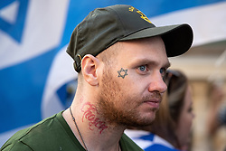 © Licensed to London News Pictures. 10/06/2018. London, UK. A man with a Star of David tattoo on his cheek amongst Jewish and pro-Israeli protesters blocking the route of the annual Al Quds day march in support of the Palestinian cause, in central London. Photo credit: Joel Goodman/LNP