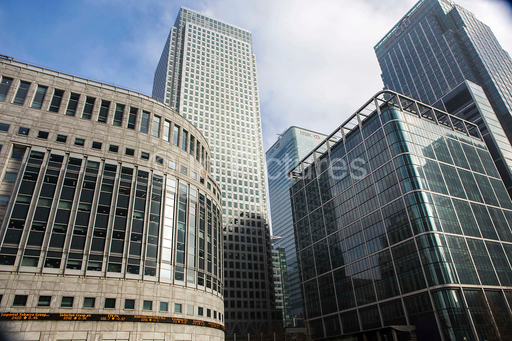 Street view from  of the iconic office buildings in the financial district of Canary Wharf, London, England, United Kingdom.   The famous One Canada Square skyscraper stands above the Thompson Reuters and Citi buildings.