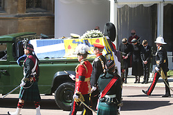 The Duke of Edinburgh's coffin, covered with his Personal Standard, is carried on the purpose built Land Rover Defender drives past (left to right) Lady Louise Windsor, the Countess of Wessex and James, Viscount Severn with heads bowed, at the Galilee Porch of St George's Chapel, Windsor Castle, Berkshire, during the funeral of the Duke of Edinburgh. Picture date: Saturday April 17, 2021.