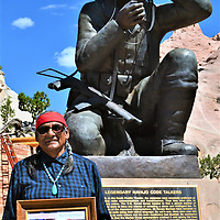 Irvin Smith of Red Rock was among several descendents of Navajo Code Talkers who attended the signing of a proclamation by the Navajo Nation three branch chiefs to honor the Navajo Code Talkers. Smith holds a group photo of the Code Talkers, who include his late dad, George Smith, and his late uncle, Albert Smitih, in front of a Code Talker sculpture at the Navajo Nation Veterans Memorial Park Monday.