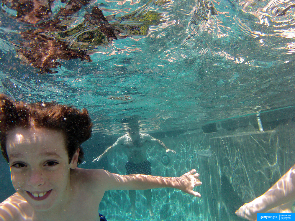 An eight year old boy swimming underwater in his back yard family swimming pool. Connecticut, USA. Photo Tim Clayton