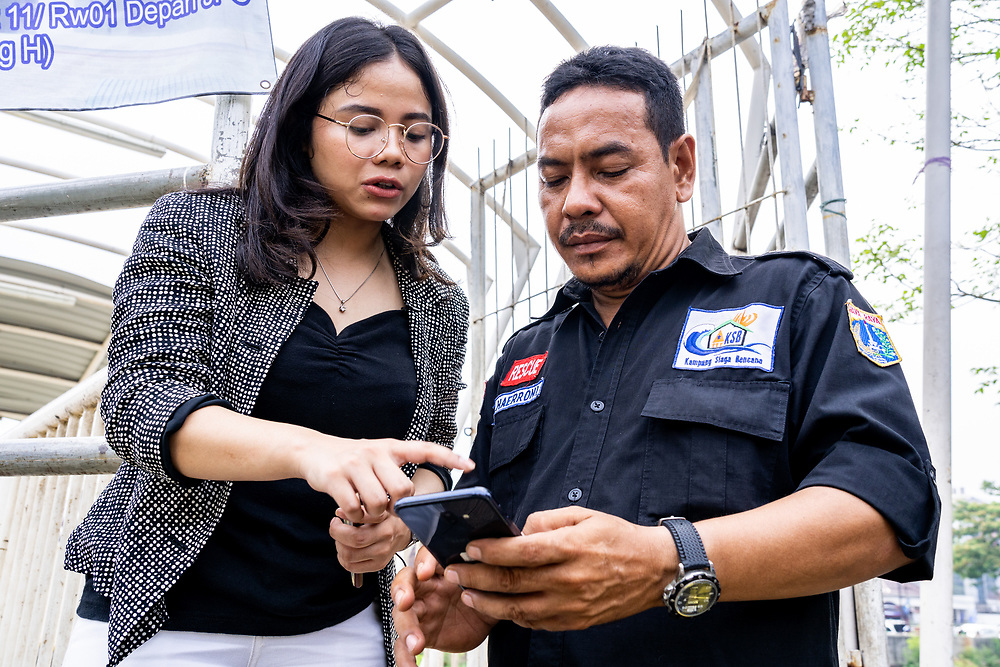 Hotniida AMW Sinambela, Research Operations Co-ordinator of Peta Bencana, demonstrates the functionality of the app on a cell phone at Kelurahan Menteng neighborhood in Jakarta an area prone to flooding.