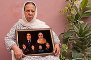 Afghanistan. Kabul. Professor Mahbuba Hoquqmal, 68, mother-in-law of murdered activist Hamida Barmaki with composite photo of her dead son, daughter in law and grandchildren made from their passport photos (the family were killed in a suicide bomb attack on the Finest supermarket).