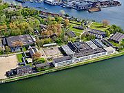 """Nederland, Noord-Holland, Zaandam, 07-05-2021; Hembrugterrein van voorheen Eurometaal, wapen- en munitiefabriek. Ook bekend als Artillerie-Inrichtingen, oorspronkelijk onderdeel van de Stelling van Amsterdam, veel van gebouwen zijn monumenten. Het witte gebouw langs het Noordzeekanaal is het HEM, de voormalige kogelfabriek en tegenwoordig 'ontmoetingsplek voor eigentijdse cultuur'.<br /> Hembrug site of the former Eurometaal, weapons and ammunition factory. Also known as Artillerie-Ininrichting, originally part of the Defense Line of Amsterdam, many of the buildings are listed buildings. The white building along the North Sea Canal is the HEM, the former bullet factory and nowadays """"meeting place for contemporary culture"""".<br /> luchtfoto (toeslag op standard tarieven);<br /> aerial photo (additional fee required)<br /> copyright © 2021 foto/photo Siebe Swart"""