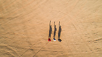 Aerial view of friends waving with their shadows in the Sharjah desert, U.A.E.