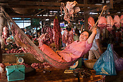 Meat seller hangs amongst her goods at the meat area of Psar Leu market. Here the meat hangs in the air and sits on the floor as the sellers, raised up, cut and sell the meat at their feet. Psar Leu market at the heart of this transport stop just outside Siem Reap to the east. This huge market entirely populated by locals is the central place to buy almost any goods, from a piece of pork to a gold bracelet. This is a covered market whose food sections bustle with energy and customers.