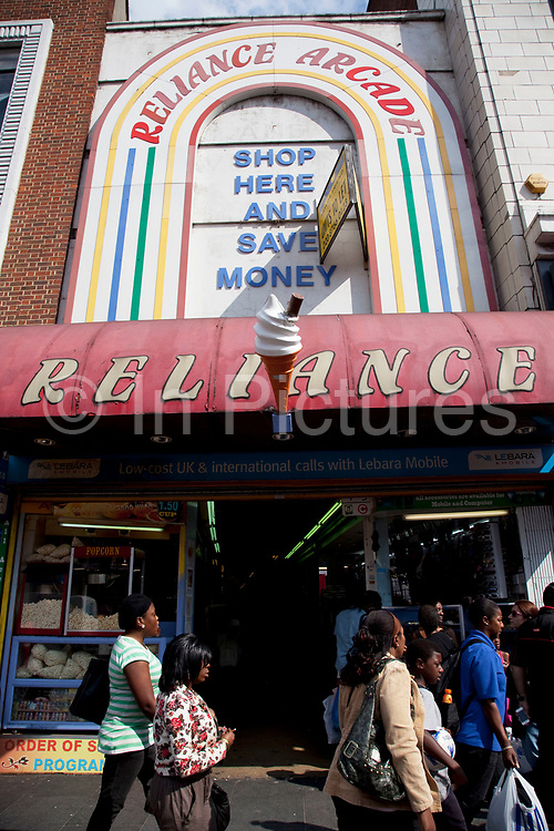 Reliance Arcade, 455 Brixton Road (c1924) provides a narrow pedestrian route from Brixton Road to Electric Lane. It incorporates the original Georgian house and has a beautiful Egyptian tomb facade to Electric Lane; it was extended forward by Ernest J Thomas in 1931. Inside there are small shops no larger than market stalls and a glazed roof provide the light. Brixton is a district in south London, England, in the London Borough of Lambeth. The area is identified in the London Plan as one of 35 major centres in Greater London. Brixton is predominantly residential with a prominent street market and substantial retail sector. It is a multiethnic community, with around 24 percent of Brixton's population being of African and Caribbean descent, giving rise to Brixton as the unofficial capital of the British African-Caribbean community.