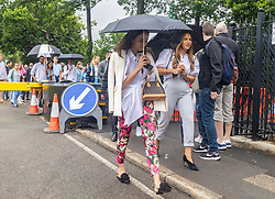 Licensed to London News Pictures. 28/06/2021. London, UK. Tennis fans brave the rain on the first day of Wimbledon. Long queues form outside the All England Lawn Tennis Club in Wimbledon, southwest London today on the first day of the Championships as weather forecasters predict thunderstorms and showers for the next three days. The 2021 AELTC Tennis Championships at Wimbledon, southwest London is back today for the first time in two years after it was cancelled last year due to the Covid-19 pandemic. However, capacity is down by 50% and fans must pre-ordered tickets with no overnight camping or queuing. Photo credit: Alex Lentati/LNP