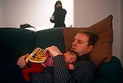 An exhausted father lays on the family sofa, snuggled up with his infant child who also slumbers on his chest. He has been reading a yellow-covered copy of the Don de Lillo novel, Libra. In the background, the wife and mother can be seen having some sort of personal crisis while the man looks very chilled out and probably  pleased to have the chance to read, snooze and have his sleeping child to comfort. It is a scene of role-reversal as the male of the family is the one left holding the baby, a scene of a modern family as opposed to the traditional Victorian or Edwardian gender.