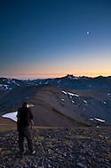 Photographer photographing the Moon at dusk over the mountain peaks of the High Sierra, Emigrant Wilderness, California